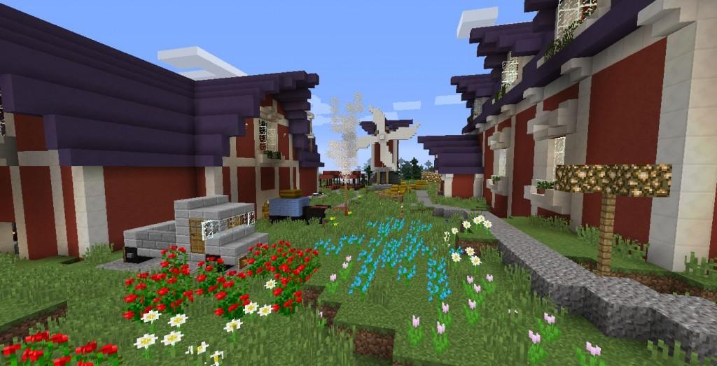 Punaisia taloja, vihreä nurmikko ja kukkia.