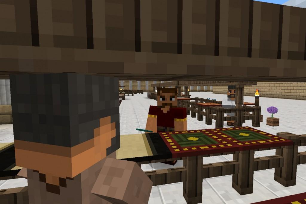 Pelihahmoja pöydän vieressä.