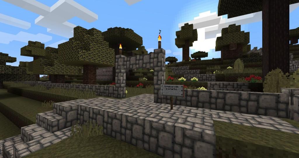 Kiviportti, jonka takana on puutarha. Kyltissä lukee Genesaretin puutarha.