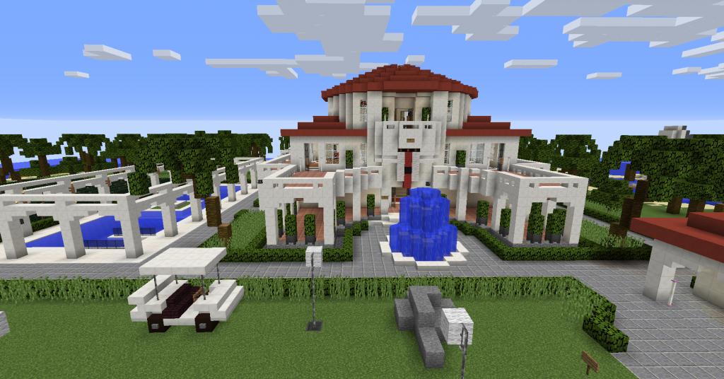 Valkoinen kartanolta näyttävä rakennus, jonka edessä on suihkulähde.