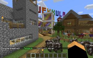 Kaupungin rakennuksia. Lehmiä aitauksessa.