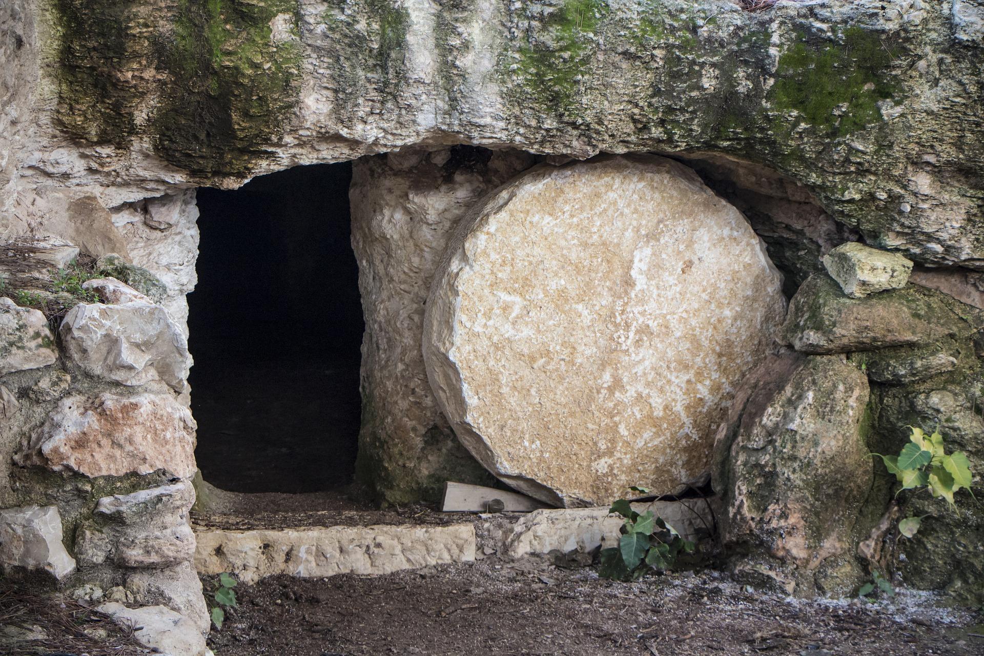 Kallio, jossa on aukko. Aukon edessä on iso, pyöreä kivi.